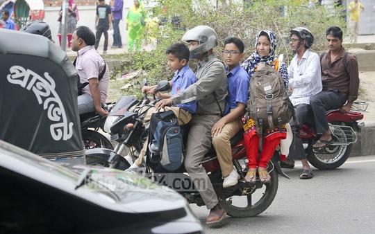 Four people ride a motorcycle flouting law, which permits only two riders. Picture taken at a road in Dhaka's Mohakhali on Tuesday. Photo: asaduzzaman pramanik