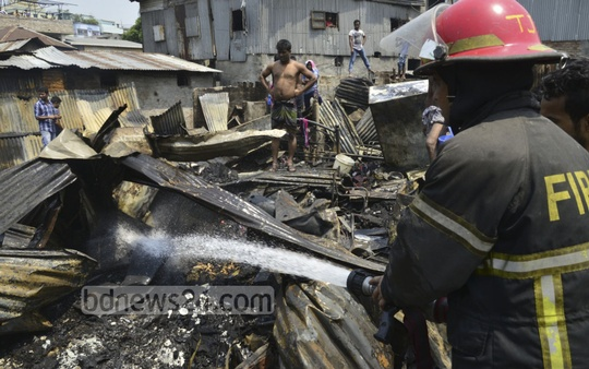 Fire Service workers busy dousing a fire at the Ambagan slum near Farmgate in Dhaka. Photo: asif mahmud ove