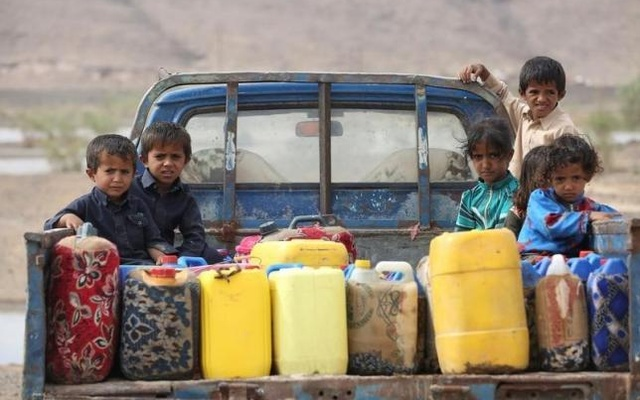 Children ride on the back of a truck loaded with water jerrycans at a camp for internally displaced people in the Dhanah area of the central province of Marib, Yemen, Apr 30, 2016. Reuters