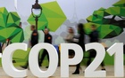 People walk walks past the COP21 logo in the Climate Generations area during the World Climate Change Conference 2015 (COP21) at Le Bourget, near Paris, France, December 1, 2015. Reuters