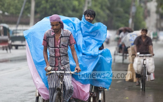 A man covers himself under a plastic sheet for protecting rickshaw passengers from the rain. Photo: nayan kumar