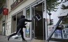 A youth throws a printer into a bank during a demonstration to protest the government's proposed labour law reforms in Nantes, France, May 26, 2016. Reuters
