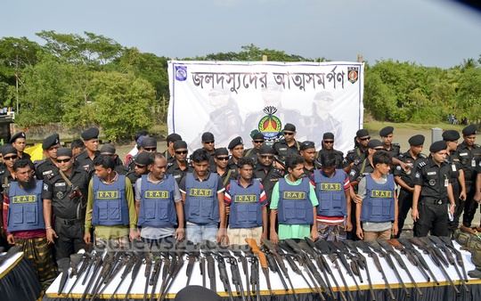 """Chief of a Sundarbans-based robbery gang, """"Master Bahini"""", and eight of his associates formally surrender by handing over weapons and ammunition to Home Minister Asaduzzaman Khan Kamal at Mongla Port in Bagerhat on Tuesday."""
