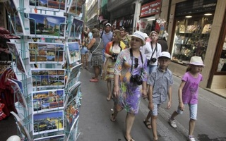 A group of tourists walk through the streets in downtown Valencia, Spain, July 23, 2015. Reuters