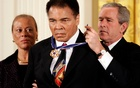 US President George W Bush awards Muhammad Ali with the Presidential Medal of Freedom, as Ali's wife Lonnie watches, during a ceremony in the White House in this Nov 9, 2005 file photo. Reuters