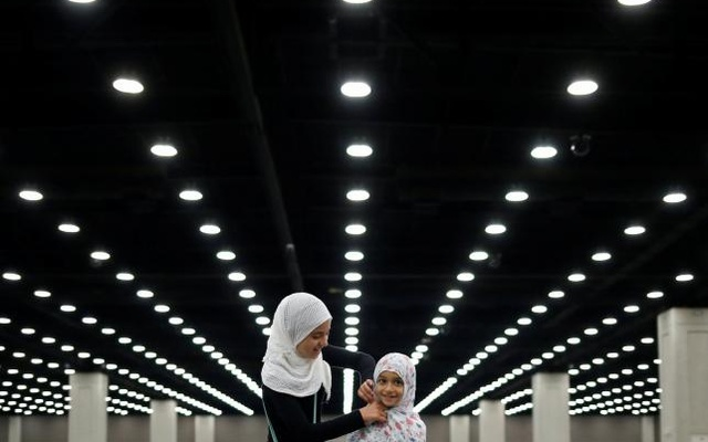 Salma Selenica, 12, (L) adjusts the headscarf of her sister Layla, 8, ahead of the jenazah, an Islamic funeral prayer, for the late boxing champion Muhammad Ali in Louisville, Kentucky, U.S. June 9, 2016. Reuters