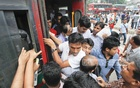 Passengers risk their lives to get on a bus at Farmgate in Dhaka on Sunday. Photo: nayan kumar