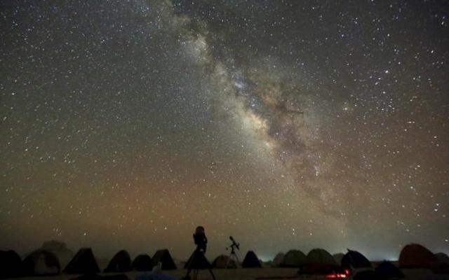 The 'Milky Way' is seen in the night sky around telescopes and camps of people over rocks in the White Desert north of the Farafra Oasis southwest of Cairo May 16, 2015. Reuters