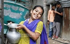 A girl is all smiles after getting water. Photo: tanvir ahammed