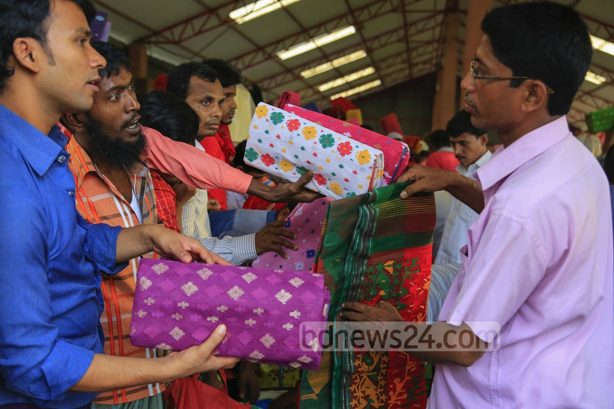 Customers checking Jamdani saree at a wholesale market in Dhaka's Demra on Friday.