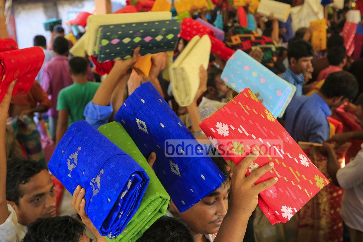 Wholesalers at Demra Jamdani Haat hold sarees up to draw buyers' attention on Friday.