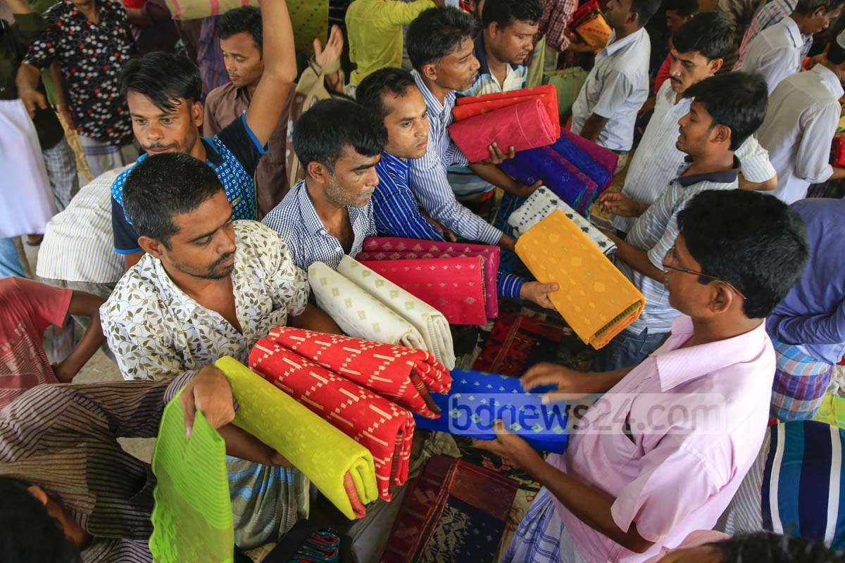 Traders have a busy time at a wholesale market of Jamdani saree at Demra beside the Shitalakkhya River on Friday.