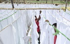 Workers hanging washed panjabis on ropes for drying.