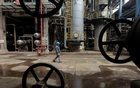 A worker walks past oil pipes at a refinery in Wuhan, Hubei province March 23, 2012. Reuters