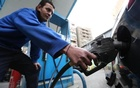 An employee holds a fuel pump nozzle as he fills up a car with fuel at a CO-OP petrol station in Cairo, Jan 13, 2015. Reuters