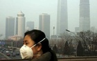 A woman wearing a mask stands by the side of a street amidst heavy smog. (File Photo)