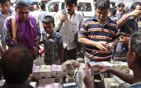Customers buy new bills at a footpath stall in Gulistan on Thursday ahead of the Eid. Photo: asif mahmud ove