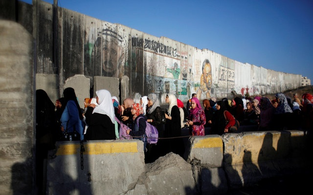 Palestinians wait to cross through Israeli Qalandia checkpoint as they make their way to attend the last Friday prayer of the holy fasting month of Ramadan in Jerusalem's al-Aqsa mosque, near the West Bank city of Ramallah July 1, 2016. reuters
