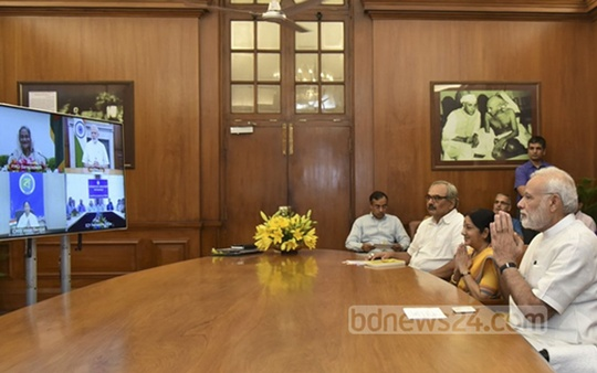 Narendra Modi, right, folds his hands in a gesture to Sheikh Hasina, top left on the TV screen, as they jointly inaugurate an integrated check post at Benapole-Petrapole border though a video conferencing on Thursday. Photo: New Delhi Correspondent