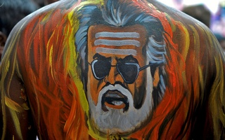 A fan with his body painted with an image of actor Rajinikanth is pictured outside a movie theatre showcasing the Tamil film