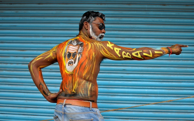 A fan with his body painted with an image of actor Rajinikanth poses outside a movie theatre showcasing the Tamil film