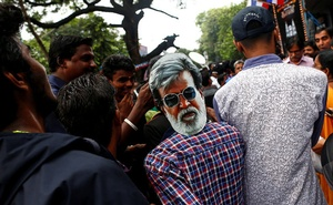 A fan wearing a mask of actor Rajinikanth waits outside a movie theatre on the eve of the release of Tamil film