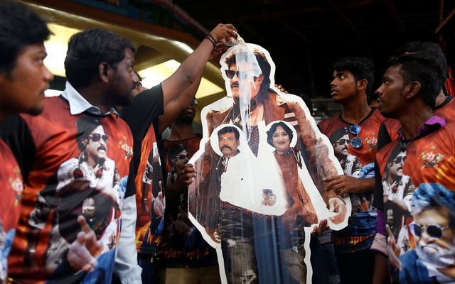 Fans pour milk on a cutout of actor Rajinikanth outside a temple on the eve of the release of Tamil film