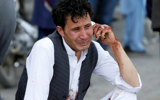 An Afghan man talks on his phone after a suicide attack in Kabul, Afghanistan July 23, 2016. Reuters