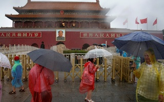 Tourists hold umbrellas as they stand in front of the Tiananmen Gate and a giant portrait of Chinese late Chairman Mao Zedong on a day of heavy rain in Beijing, China, July 20, 2016. Reuters