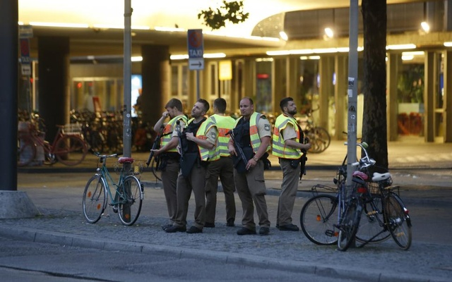 Police officers stand guard outside the main train station following a shooting rampage at the Olympia shopping mall in Munich. Reuters