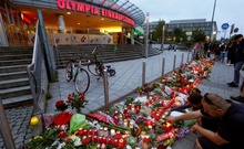 People light candles beside flowers laid in front of the Olympia shopping mall, where yesterday's shooting rampage started, in Munich, Germany July 23, 2016. Reuters