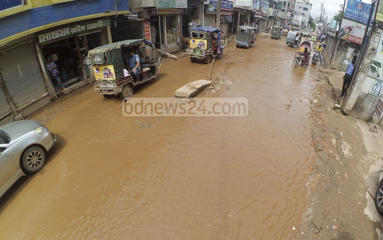 The worst sufferers of waterlogging, residents are made to wade through the road for months on end. Photo: abdul mannan.