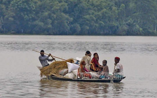 A family escapes the floods at Sarkarpara in Ulipur upazila of Kurigram. Photo: mostafigur rahman