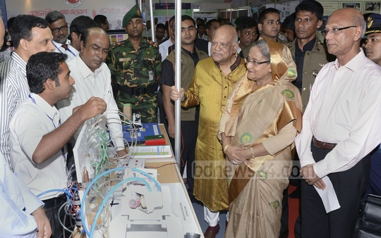 Prime Minister Sheikh Hasina, flanked by Finance Minister AMA Muhith, left, and Education Minister Nurul Islam Nahid, is briefed on innovative initiatives at 'Civil Service in Development Innovation-2016' Summit on Thursday. Photo: PMO