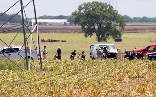The partial frame of a hot air balloon is visible above a crop field as investigators comb the wreckage of an accident that left at least 16 people killed dead when the balloon crashed in Maxwell, Texas, US, July 30, 2016. Ralph Barrera/Austin American-Statesman/via Reuters