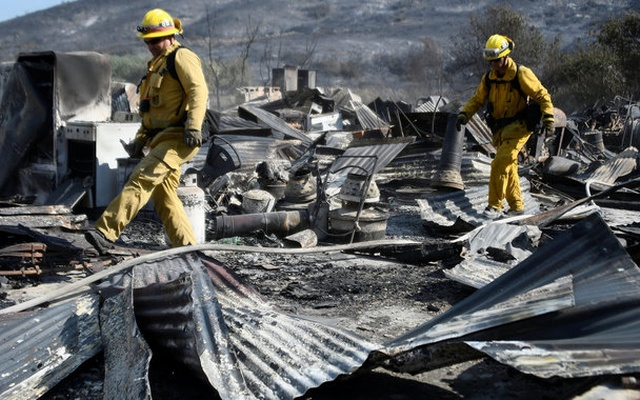 Firefighters walk over the remains of a barn destroyed by the so-called Blue Cut Fire in the San Bernardino National Forest in San Bernardino County, California, US August 18, 2016. REUTERS