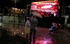 People stand in the rain while watching the 2016 Rio Olympics closing ceremony on a large screen in Rio de Janeiro August 21, 2016. Reutes