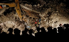 Rescuers work in the night at a collapsed house following an earthquake in Pescara del Tronto, central Italy, August 24, 2016. Reuters