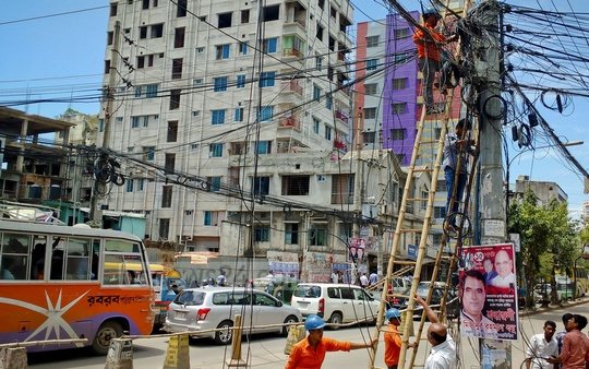 Dhaka Electric Supply Company Limited remove satellite and internet cables considered risky from both sides of the Gulshan-Badda Link Road on Saturday. Photo: asaduzzaman pramanik