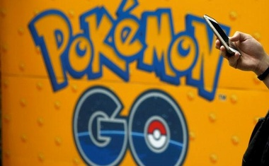 A man uses a mobile phone in front of an advertisement board bearing the image of Pokemon Go at an electronic shop in Tokyo, Japan, July 27, 2016. Reuters