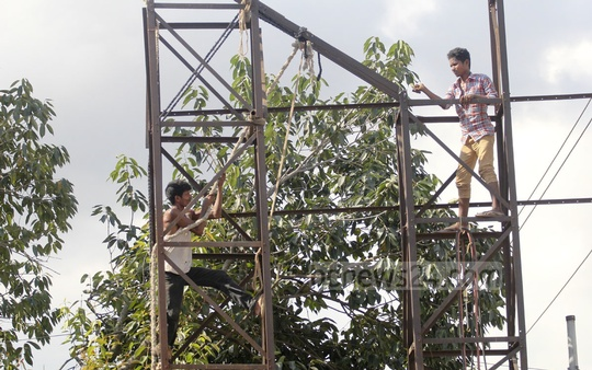Workers remove an illegal billboard without any safety measures in Dhaka's Mohakhali area. Photo: asif mahmud ove