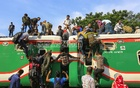Low-income people overloading the roof of a train at Dhaka's Airport Rail Station on Friday as they travel, risking their lives, to their villages ahead of the Eid celebration.