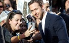 Actor Ryan Gosling greets fans as he arrives on the red carpet for the film La La Land. Reuters