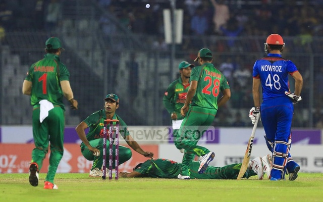 Mashrafe Bin Mortaza falls on his ankle after his front foot got tangled with the rear one on his delivery stride. His teammates rush to him to attend their captain. Photo: muhammad mostafigur rahman