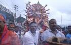 The idol of Durga being borne from the capital's Bongshal to the immersion site in Waizghat.