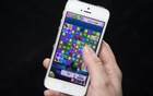 A woman poses for a photo illustration with an iPhone as she plays Candy Crush in New York February 18, 2014. Reuters