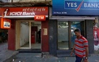 A man walks past ICICI Bank and Yes Bank automated teller machines (ATMs) in New Delhi, India, Oct 20, 2016. Reuters