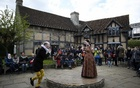 Tourists watch actors perform at the house where William Shakespeare was born during celebrations to mark the 400th anniversary of the playwright's death in Stratford-Upon-Avon, Britain, April 23, 2016. Reuters