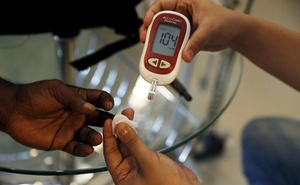 A paramedic (R) checks the blood sugar level of a patient at SS Diabetes. Reuters File Photo