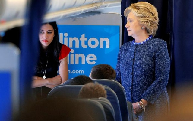 U.S. Democratic presidential nominee Hillary Clinton talks to staff members, including aide Huma Abedin (L), onboard her campaign plane in White Plains, New York, U.S. October 28, 2016. Reuters